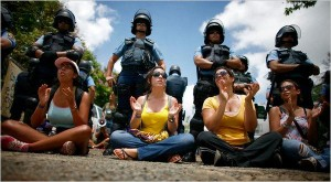 Students protesting budget cuts at the University of Puerto Rico, San Juan campus.  Riot police officers stand behind them.  (Photo: Ricardo Arduengo / Associated Press)