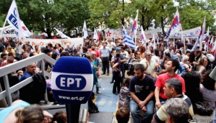 People gather outside the headquarters of the Greek public broadcaster ERT in support of staff