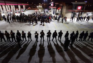 Police officers in riot gear hold a line as they watch demonstrators protest the shooting death of Michael Brown and 18-year-old Vonderrit Myers Jr. in St. Louis, Missouri on October 12, 2014.  (Photo: Joshua Lott / AFP / Getty Images)