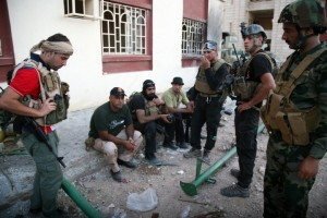 Iraqi security forces rest on a sidewalk following clashes with jihadists in Ramadi in September (Photo: Azhar Shallal/AFP/Getty Images)