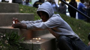 A boy lights candles during a vigil to remember Vonderrit D. Myers, Thursday, Oct. 9, 2014, in St. Louis. (Photo: Jeff Roberson / Associated Press)