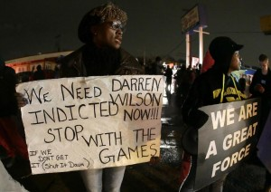 Protesters hold signs Saturday, Nov. 22, along a stretch of road where protests occurred following the August shooting of Michael Brown, an unarmed black teenager, by a white police officer in Ferguson, Missouri.  (AP Photo / Charlie Riedel)