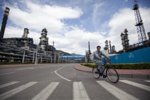 A worker cycles through the China Petroleum & Chemical Corp (Sinopec) refinery in Beijing. (Photo: Nelson Ching / Bloomberg)