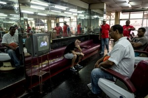 Watching President Raúl Castro's speech in a barbershop in Havana on Saturday. Mr. Castro declared victory for the Cuban revolution and thanked President Obama for opening a new chapter, while also asserting that restored relations with the United States would not mean the end of Communist rule in Cuba (Photo: Meridith Kohut for The New York Times)