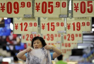An employee folds a shirt under price tags at a supermarket in Hefei, Anhui province. (Photo: REUTERS/Stringer