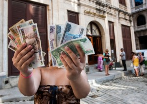 A woman shows Cuban pesos CUP, left, and convertible pesos CUC, right, on October 22, 2013 in Havana. (Photo: Yamil Lage / AFP via Getty Images)
