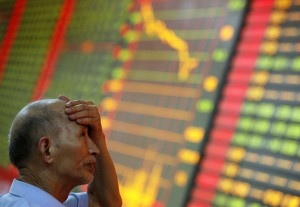 A man gestures as he watches stock activity at a stock exchange in Huaibei, China. (Photo: STR / AFP / Getty Images)