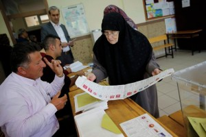 A woman looks at a ballot paper before she votes in Konya, Turkey on June 7, 2015. (Photo: Umit Bektas / Reuters)