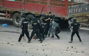Riot police beating protestors in Linshui (Photo: telegraph.co.uk)
