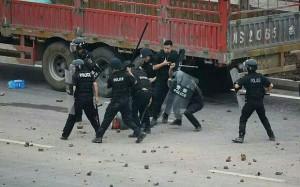 Riot police beating protestors in Linshui (Photo: telegraph.co.uk)