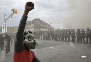 A demonstrator raises his fist as police stand in formation as a store burns, Monday, April 27, 2015, during unrest following the funeral of Freddie Gray in Baltimore.  (Photp: AP / Patrick Semansky)