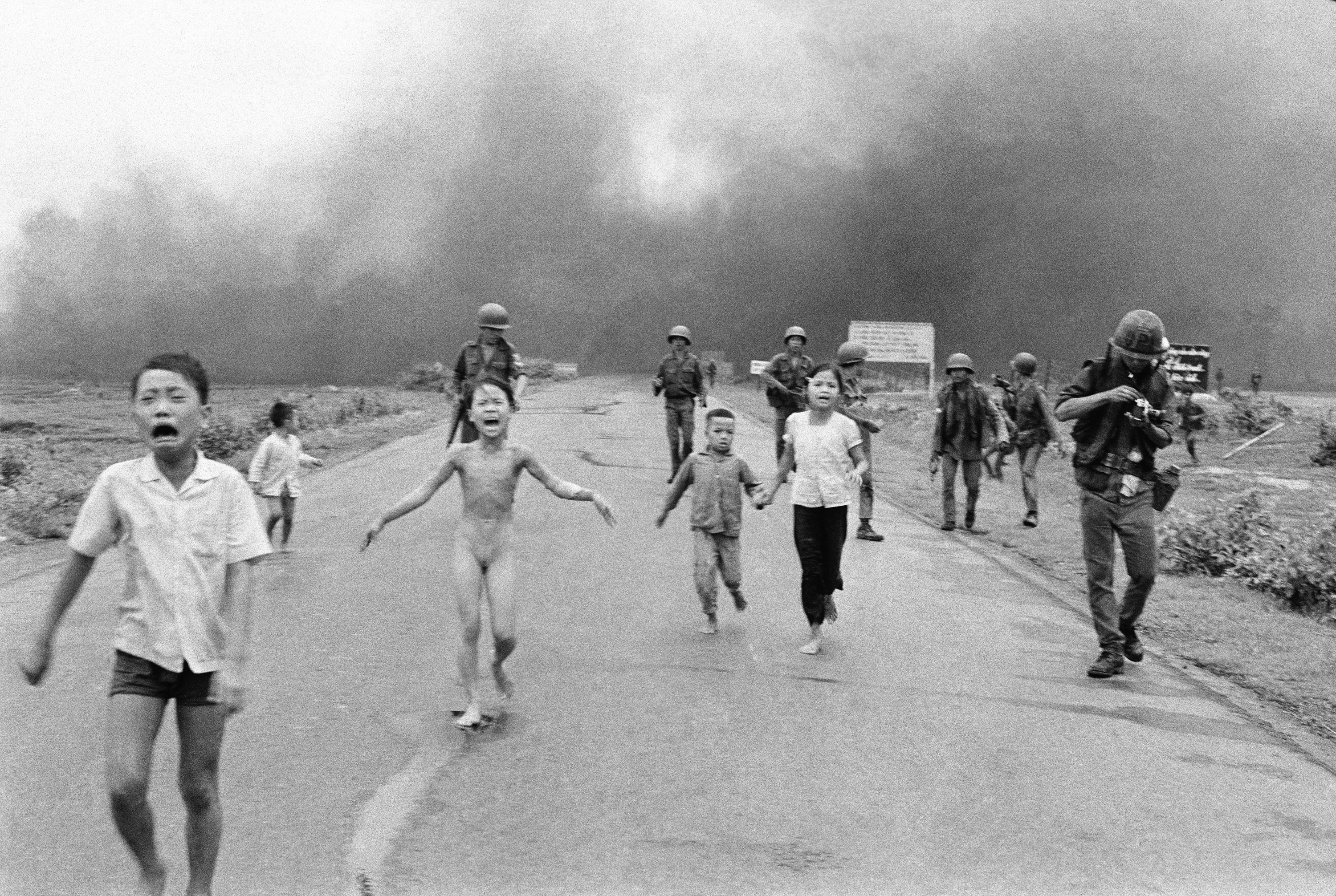 South Vietnamese forces follow after terrified children, including 9-year-old Kim Phuc, center, as they run down Route 1 near Trang Bang after an aerial napalm attack on suspected Viet Cong hiding places, June 8, 1972. A South Vietnamese plane accidentally dropped its flaming napalm on South Vietnamese troops and civilians. The terrified girl had ripped off her burning clothes while fleeing. The children from left to right are: Phan Thanh Tam, younger brother of Kim Phuc, who lost an eye, Phan Thanh Phouc, youngest brother of Kim Phuc, Kim Phuc, and Kim's cousins Ho Van Bon, and Ho Thi Ting. Behind them are soldiers of the Vietnam Army 25th Division. (AP Photo/Nick Ut)