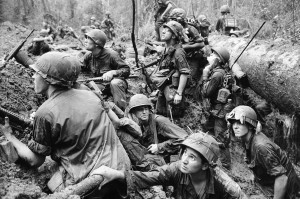 American infantrymen crowd into a mud-filled bomb crater and look up at tall jungle trees seeking out Viet Cong snipers firing at them during a battle in Phuoc Vinh, north-Northeast of Saigon in Vietnam's War Zone D, June 15, 1967. (AP Photo / Henri Huet)