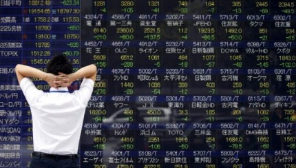 A man looks at a stock quotation board outside a brokerage in Tokyo, August 24, 2015. Asian stocks dived to 3-year lows on Monday as a rout in Chinese equities gathered pace, hastening an exodus from riskier assets as fears of a China-led global economic slowdown roiled world markets.  REUTERS/Toru Hanai
