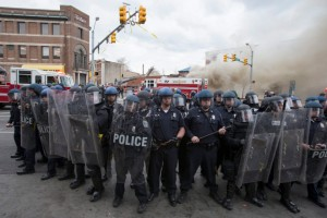 Police form a line in front of a building on fire during protests of the death of Freddie Gray in Baltimore, Maryland (Photo: EPA / Michael Reynolds)