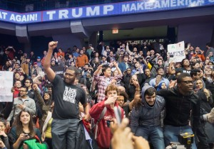 The protester in the front left of this photo is wearing a Black Lives Matter shirt; the poster in the far right is a reference to Trump's comments about immigrants being rapists. Credit:Scott Olson/Getty