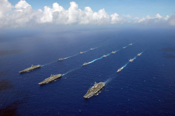 060618-N-8492C-221 Philippine Sea (June 18, 2006) - The Kitty Hawk, Ronald Reagan and Abraham Lincoln Carrier Strike groups sail in formation, as Air Force, Navy and Marine Corps aircraft fly overhead during the photo portion of Exercise Valiant Shield 2006. Valiant Shield focuses on integrated joint training among U.S. military forces, enabling real-world proficiency in sustaining joint forces and in detecting, locating, tracking and engaging units at sea, in the air, on land and cyberspace in response to a range of mission areas. U.S. Navy photo by Chief Photographer's Mate Todd P. Cichonowicz (RELEASED)