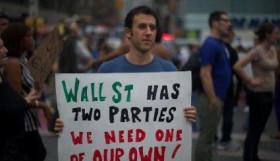 Socialist Alternative member Jesse L holds a sign in Zuccotti Park.