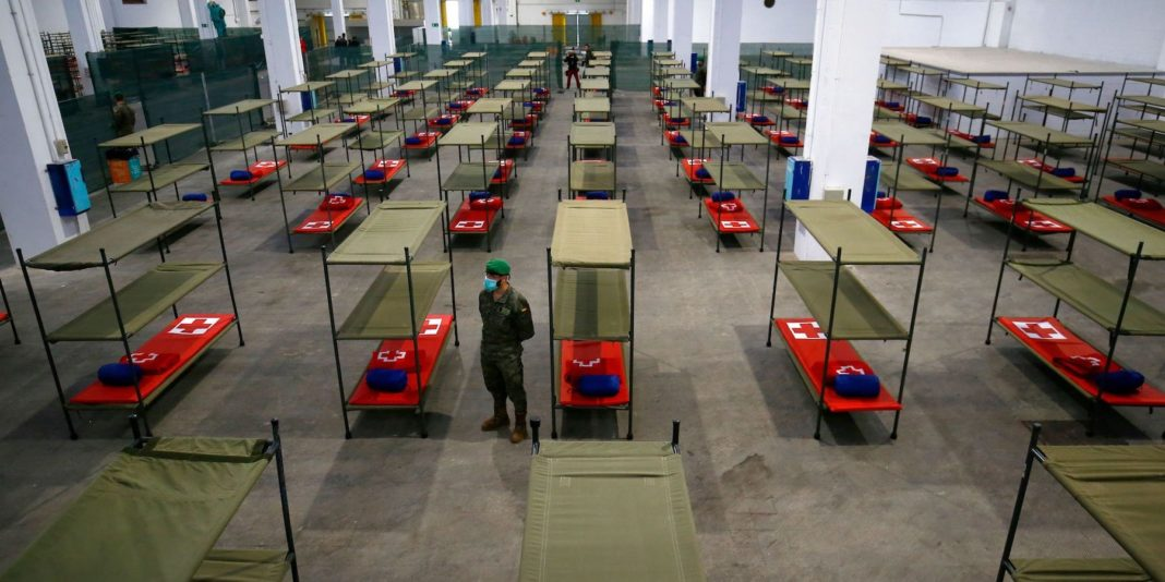 A Spanish soldier standing next to beds set up at a temporary hospital for vulnerable people in Barcelona. PAU BARRENA/AFP via Getty Images