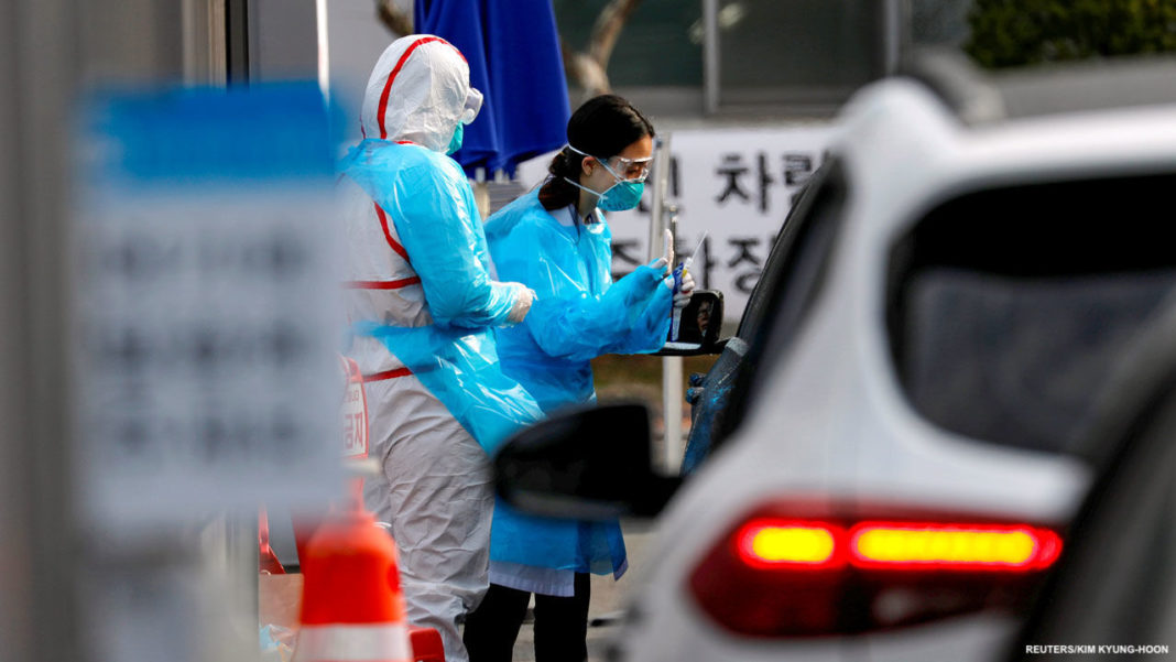 A medical staff member in protective gear prepares to take samples from a visitor in a car at a 'drive-thru' testing center for the novel coronavirus disease of COVID-19 in Yeungnam University Medical Center in Daegu, South Korea, March 3, 2020. REUTERS/Kim Kyung-Hoon - RC28CF933C88